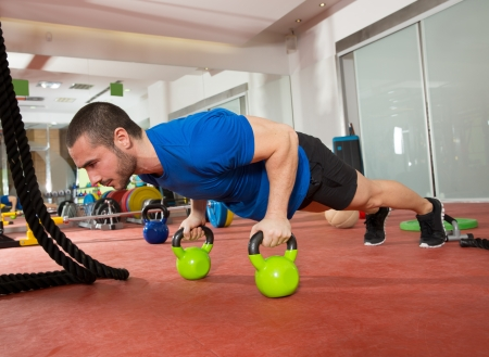 push up: Crossfit fitness man push ups Kettlebells pushup exercise at gym workout