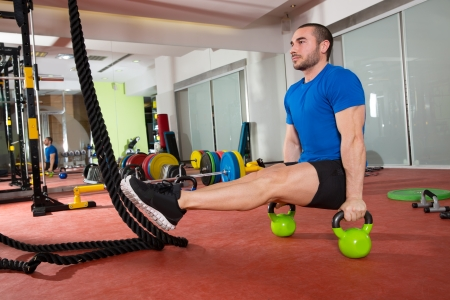 Crossfit fitness man L-sits Kettlebells L sits exercise at gym workout