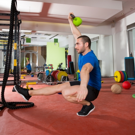 Crossfit fitness man balance Kettlebells with one leg exercise at gym workout Stock Photo