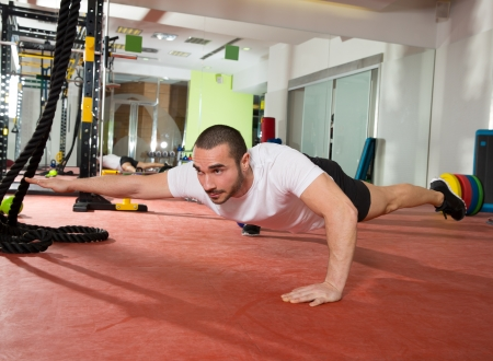 push ups: Crossfit fitness man balance push ups with one leg and arm up exercise at gym workout Stock Photo
