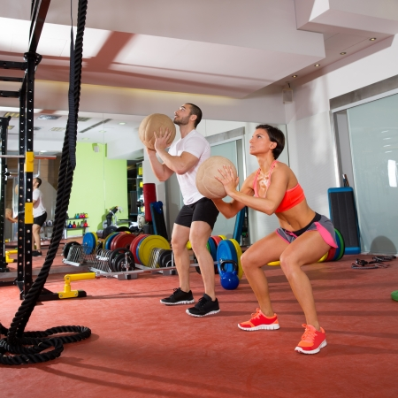 Crossfit ball fitness workout group woman and man at gym photo