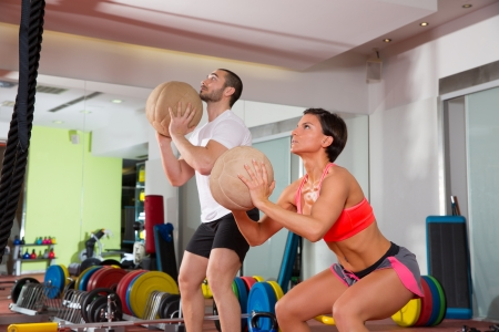 trainer: Crossfit ball fitness workout group woman and man at gym