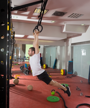 Crossfit fitness dip ring swing exercise man workout at gym photo