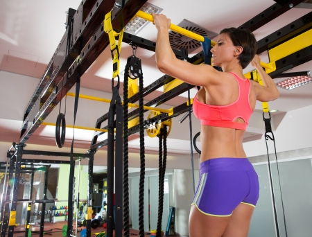 bodybuilder: Crossfit fitness toes to bar woman pull-ups 2 bars with TRX foot assistant