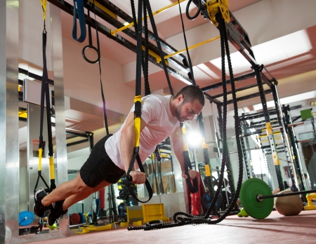 fit: Crossfit fitness TRX push ups man workout at gym
