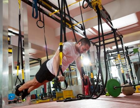 cross bar: Crossfit fitness TRX push ups man workout at gym