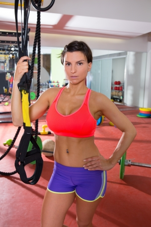 Crossfit fitness woman standing at gym holding trx posing photo