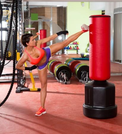 piernas sexys: Crossfit fitness mujer kick boxing con el saco de boxeo rojos en el gimnasio Foto de archivo