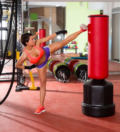 punching: Crossfit fitness woman kick boxing with red punching bag at gym