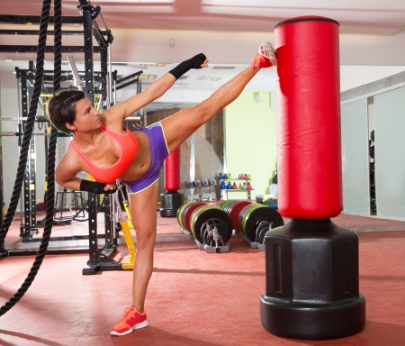 gymnasium: Crossfit fitness woman kick boxing with red punching bag at gym