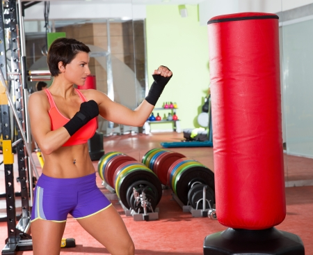 Crossfit fitness woman boxing with red punching bag at gym photo