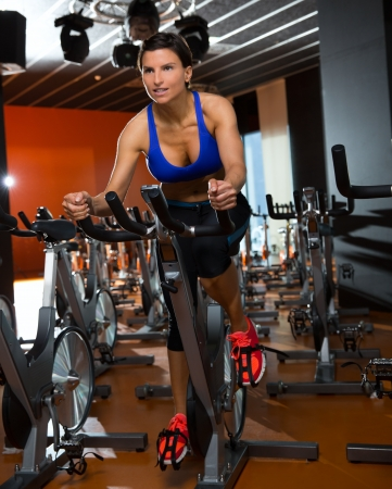 Aerobics spinning woman exercise workout at bikes gym photo