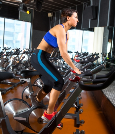 cardio: Aerobics spinning woman exercise workout at bikes gym