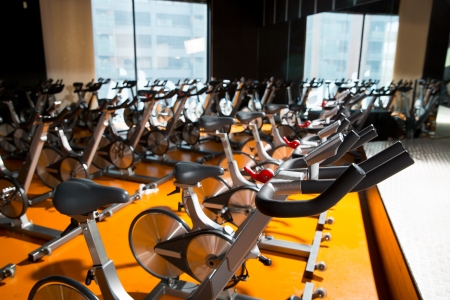 health resort: Aerobics spinning exercise bikes gym room with many in a row