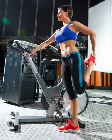 Aerobics spinning monitor trainer woman stretching exercises after workout at gym photo
