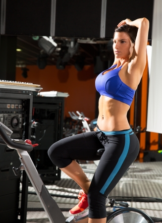 sportswear: Aerobics spinning monitor trainer woman stretching exercises after workout at gym