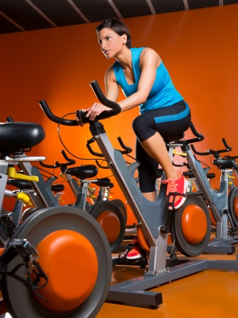 cardio: Aerobics spinning woman exercise workout at orange bikes gym