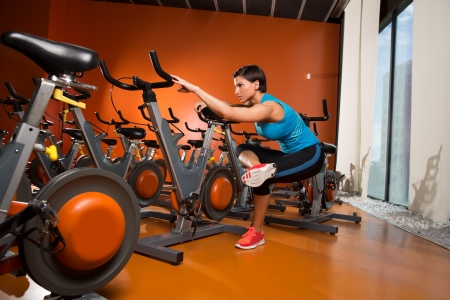 Aerobics spinning woman stretching exercises after workout at gym photo