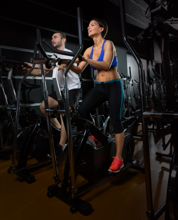 cardio fitness: elliptical walker trainer man and woman at black gym training aerobics exercise