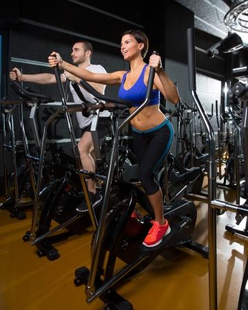 eliptica: caminador el�ptico hombre entrenador y mujer en el gym ejercicio aer�bicos entrenamiento negro Foto de archivo