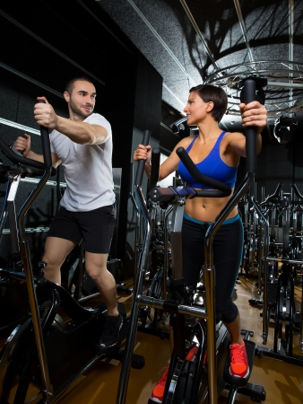 elliptical: elliptical walker trainer man and woman at black gym training aerobics exercise