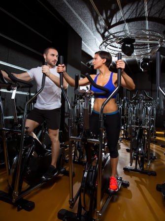 walkers: elliptical walker trainer man and woman at black gym training aerobics exercise