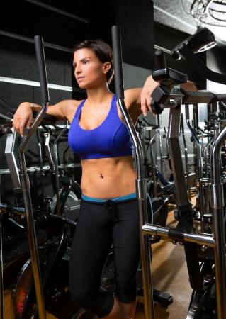 eliptica: caminador elíptico Mujer entrenador posando en el gimnasio negro relajado después del ejercicio aeróbicos Foto de archivo
