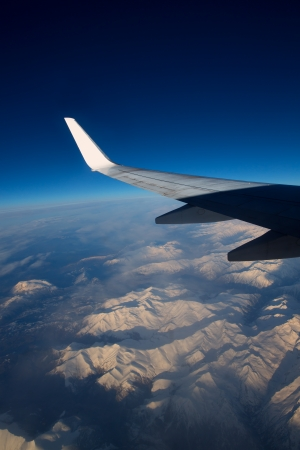 aircraft flying over snowed mountains of Pyrenees between France and Spain photo