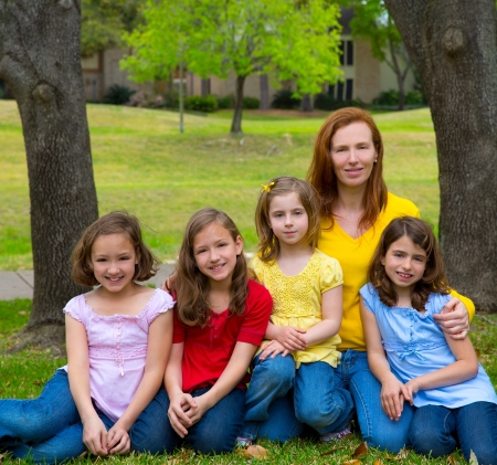 twin sister: Mother teacher with daughter pupils in playground park group portrait on lawn Stock Photo