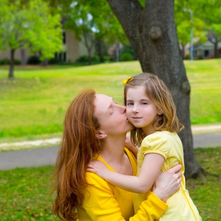 parentage: Mother kissing her blond daughter in green park outdoor dressed in yellow