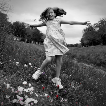 happy children girl jumping on spring poppy flowers meadow with motion blur photo