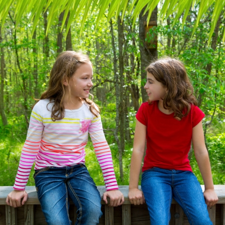 children sister friends talking relaxed sitting on the jungle park forest outdoor photo