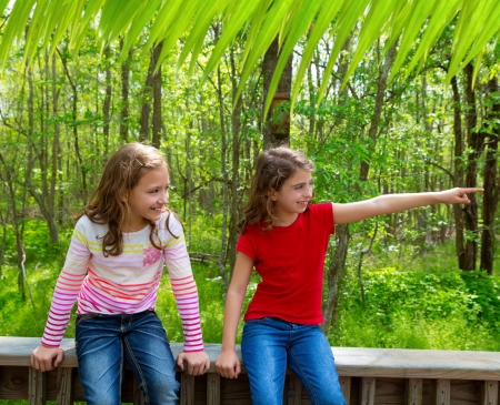 children sister friends playing relaxed pointing finger to jungle park forest outdoor photo