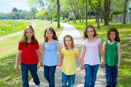 walking in park: Children group of sisters girls and friends walking happy in the park outdoor Stock Photo