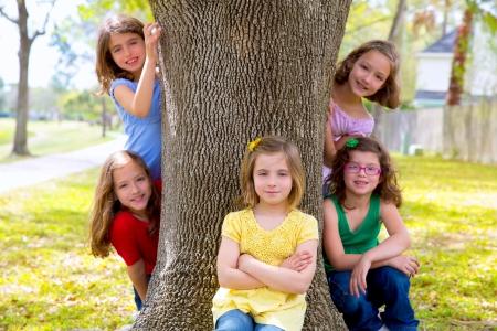 Kinderen groep zusters meisjes en vrienden spelen op boomstam in het park buiten Stockfoto