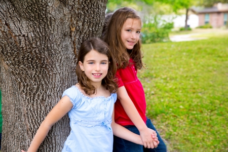Children group friend girls friends playing on tree trunk at the park outdoor photo