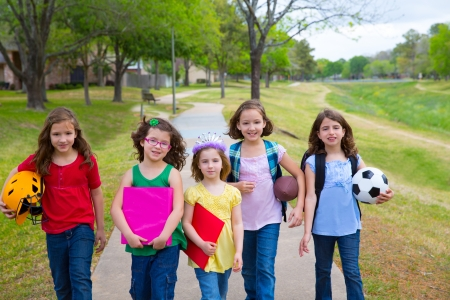 Children kid girls walking to schoool with sport balls folders and backpacks in outdoor park photo