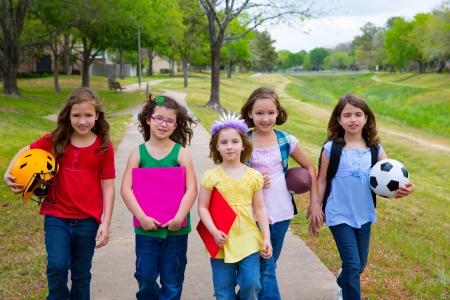 Kinderen kid meisjes lopen naar schoool met sportballen mappen en rugzakken in het park buiten