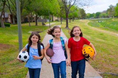 niños caminando: Ni?os ni?as ni?o caminando a schoool con bolas de carpetas y mochilas deportivas en el parque al aire libre