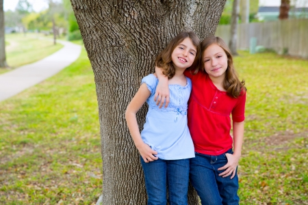 blue jeans kids: children kid friend girls hug relaxed happy smiling in a park tree outdoor