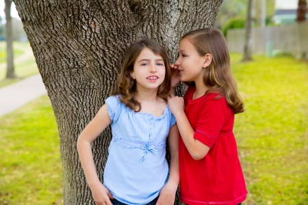 dido: children kid friend girls whispering ear playing smiling in a park tree outdoor Stock Photo