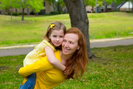 Daughter and mother piggyback smiling happy in park outdoor photo
