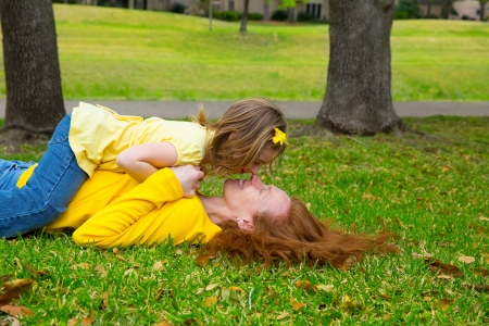 Daughter and mother nose kissing lying on park lawn outdoor photo
