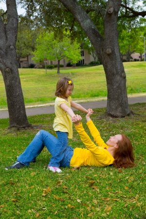 Daughter and mother playing lying on park lawn outdoor dressed in yellow photo