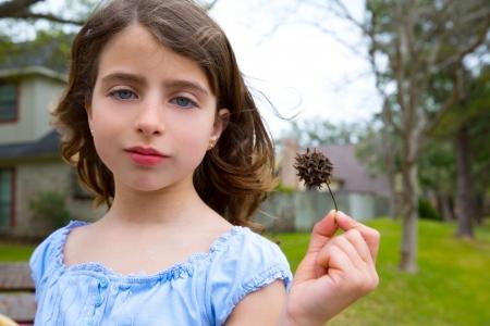 �spiked: Retrato de ni�a con American sweetgum pinchos de frutas en el parque Foto de archivo