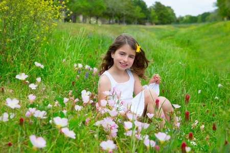 beautiful children girl on spring meadow with poppy flowers photo