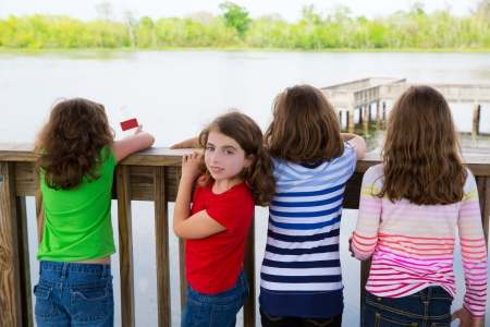 Children girls rear view looking at lake on railing and one looking behind photo