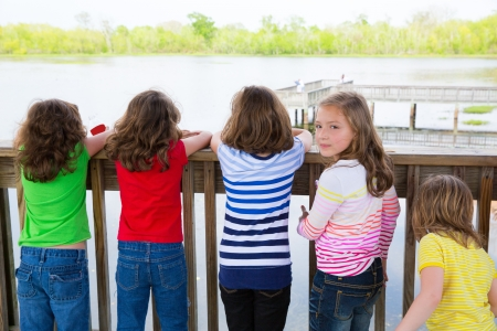 team from behind: Children girls rear view looking at lake on railing and one looking behind