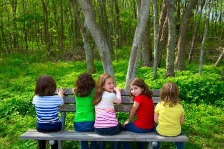 niños sentados: Niños hermana y amiga niñas sentados en el banco del parque mirando bosque y sonriente Foto de archivo