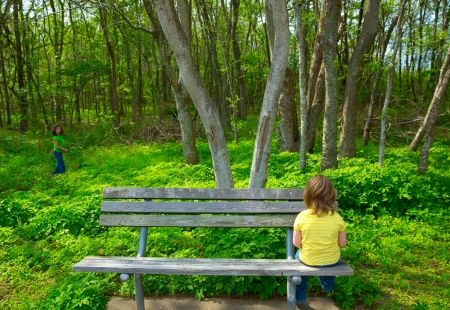 Lonely children sad looking the forest girl sitting at the park bench photo